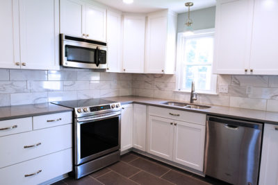 white kitchen, marble back splash, large grey tile floor
