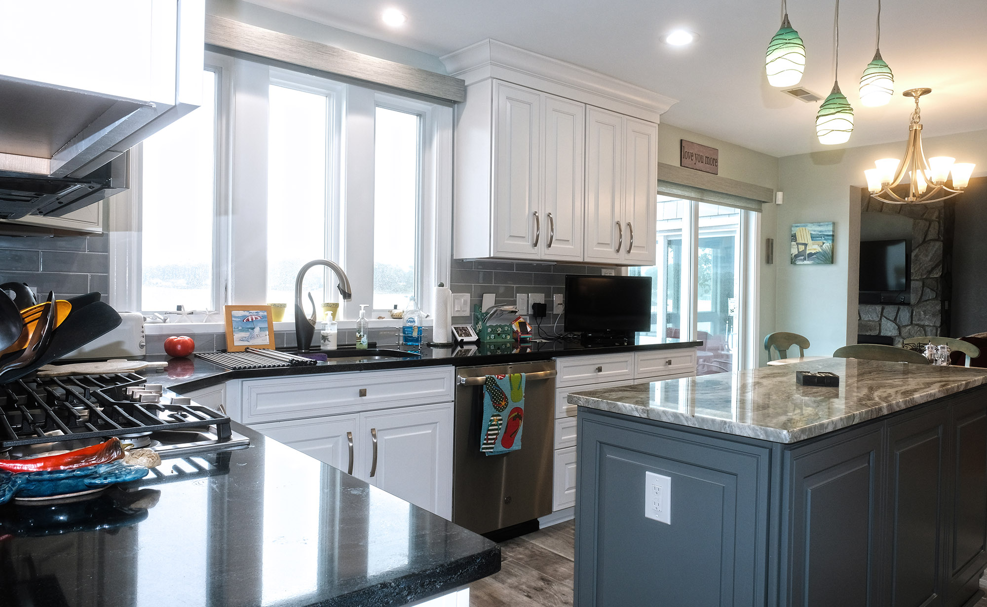 Kitchen remodel, two tone cabinets, wood look tile floor, opened up to living area.
