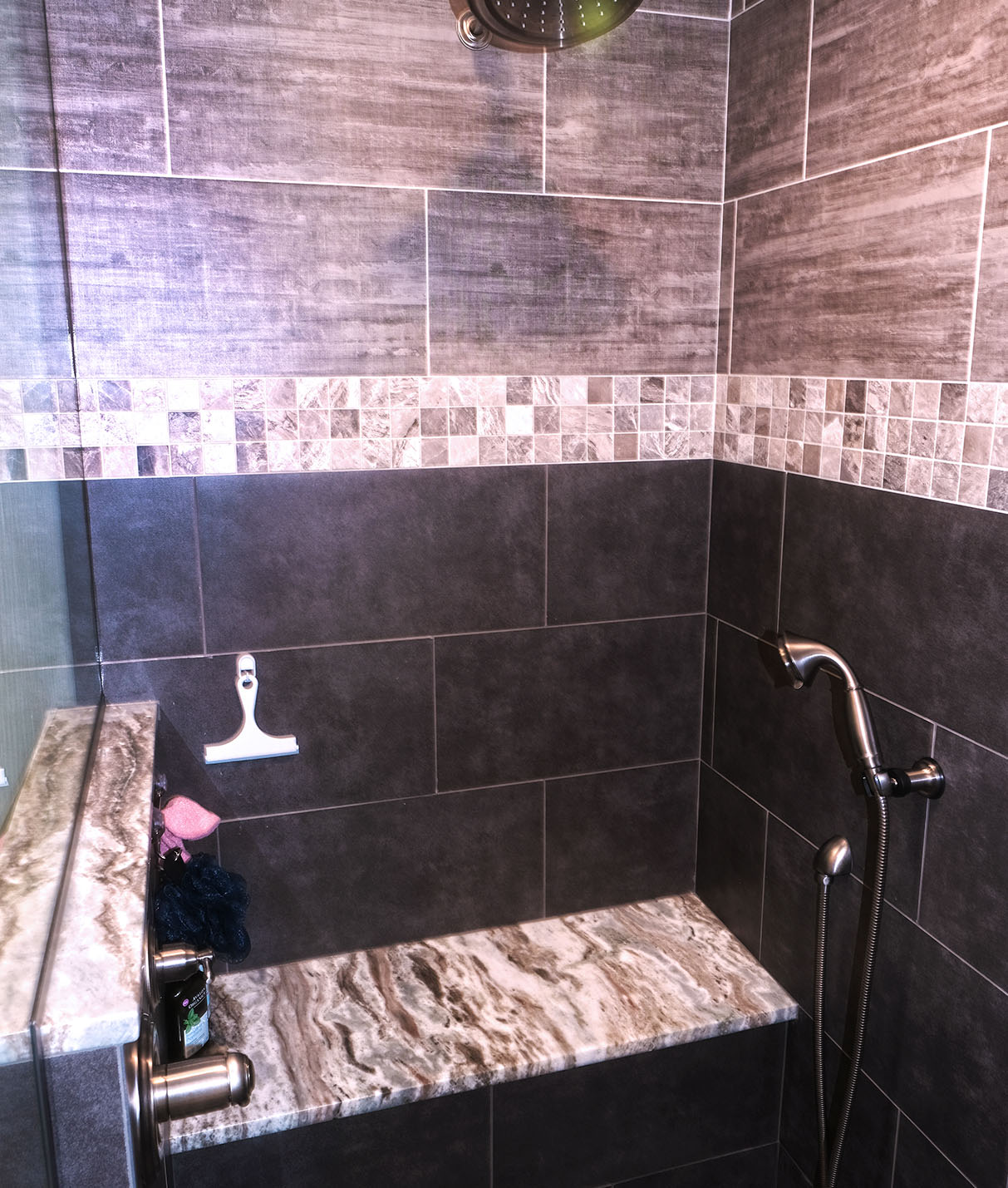 walk-in shower with bench seating and glass doors. Also includes a hand held spray plus a large rain head shower fixture.