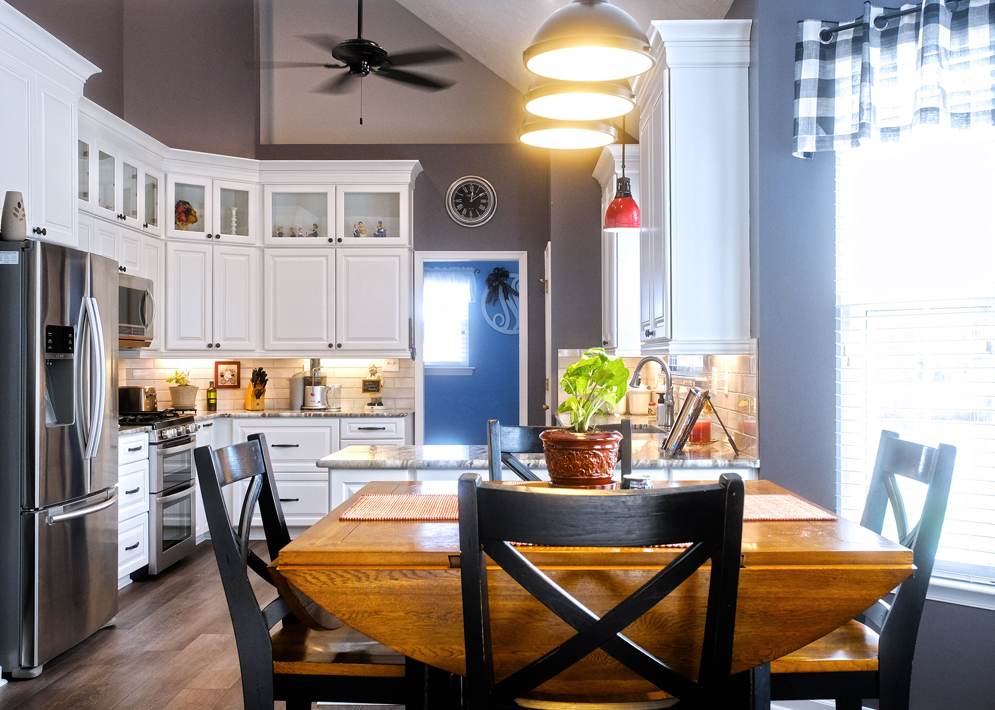 Kitchen remodel with white cabinets, tall uppers with decorative glass doors at the top. Vaulted Ceiling, stainless steel appliances, granite countertops, open concept.